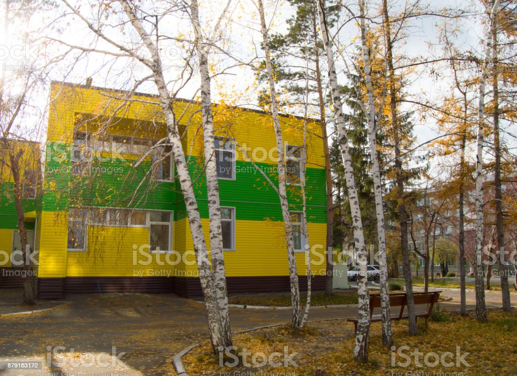 The two-storied building covered with beautiful yellow and green siding stock photo