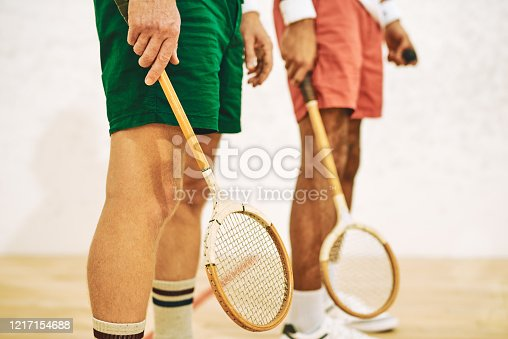 Cropped shot of two men holding their racquets at a squash court