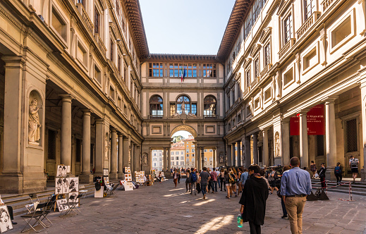 Florence, Italy - October 5, 2016: Florence, Italy - Oct 5, 2016. Tourists browsing through The Uffizi Gallery museum in Florence, and walking toward the Arno river.