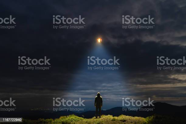 Photo of The UFO shines on a male standing on the mountain