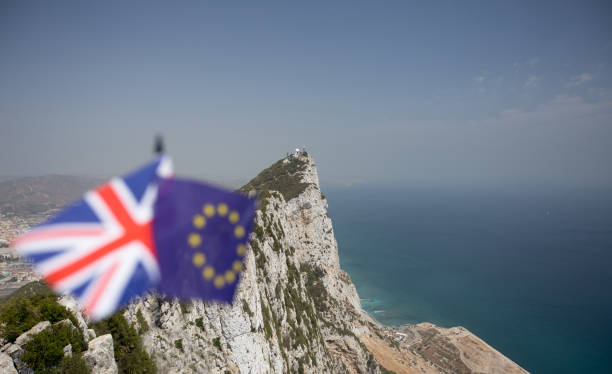 the union jack and the flag of the european union with the rock of gibraltar in the background, indicating the dispute over its sovereignty and the effects of brexit with plenty of copyspace - outcrop stock pictures, royalty-free photos & images