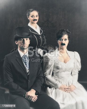 Old family photo where the Mother and daughter wear victorian mustaches.