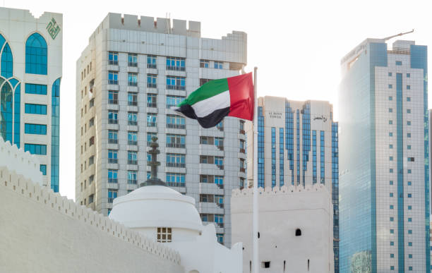 the united arab emirates flag waving in the city at sunset - uae national day стоковые фото и изображения