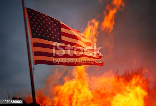 Flag of the USA and fire behind