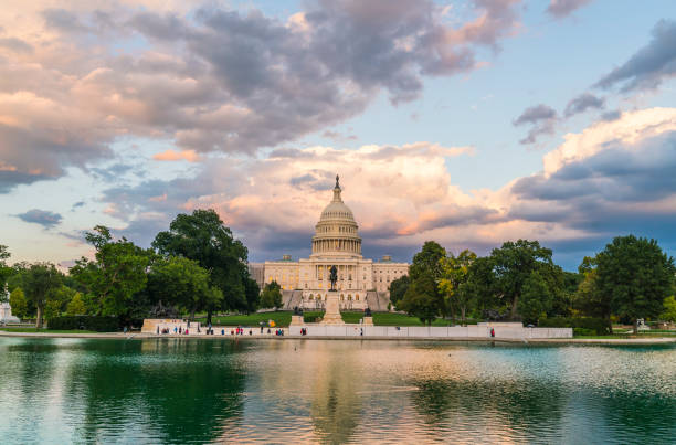 The United States Capitol building at sunset wirh reflection in water. stock photo