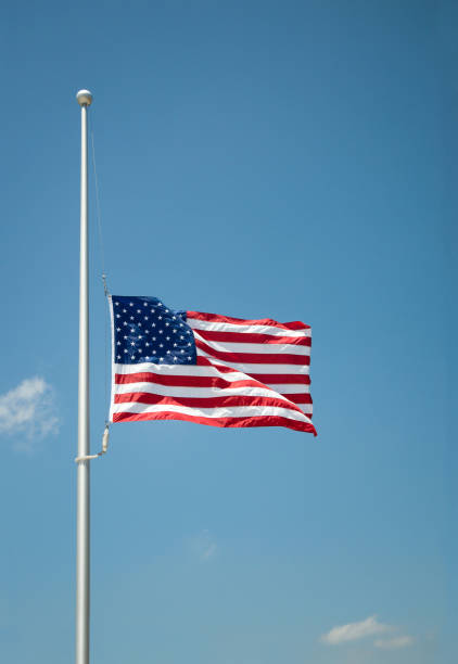 The United States flag at half-mast The United States flag flying at half-mast or half-staff on a flagpole. Blue sky background with copy space. flagpole stock pictures, royalty-free photos & images