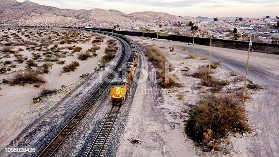 The iconic and controversial iron border wall between the USA and Mexico close to the railroad with a passing freight train.