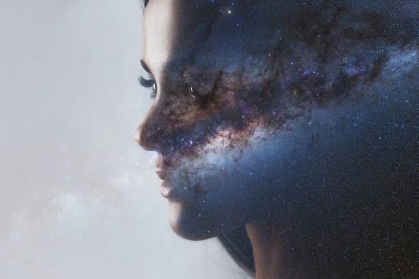 El universo dentro de nosotros, el perfil de una joven y el espacio, el efecto de la doble exposición. - foto de stock