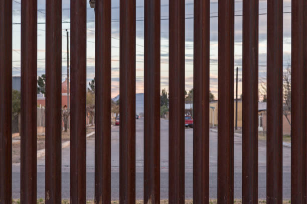 The US Border with Mexico Looking at the border fence between the USA and Mexico, with a town in Mexico visible on the other side international border barrier stock pictures, royalty-free photos & images