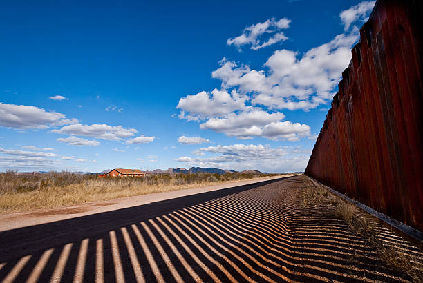 Shadows Cast Across the USA - Mexico Border The USA-Mexico Border Fence separates people in Douglas, Arizona, USA from their neighbors and family in Agua Prieta, Sonora, Mexico. international border barrier stock pictures, royalty-free photos & images
