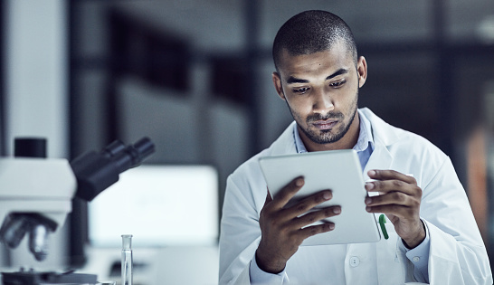 Shot of a scientist recording his findings on a digital tablet