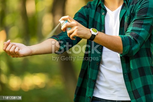 Young man spraying mosquito insect repellent in the forrest, insect protection. Mosquito repellent. Male using insect repellent spray from bootle in forest.