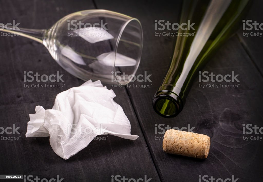used white crumpled paper napkin and an empty wine bottle with cork...