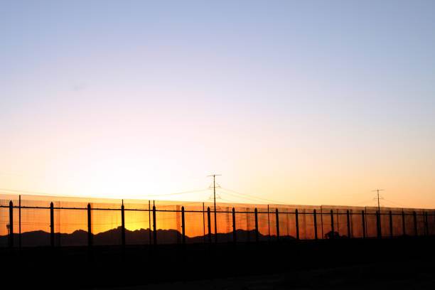 The U.S/Mexico Border Beauty The border fence at sunset on the United States side of the lower valley in El Paso, Texas facing towards the Juarez,Mexico Mountains. international border barrier stock pictures, royalty-free photos & images