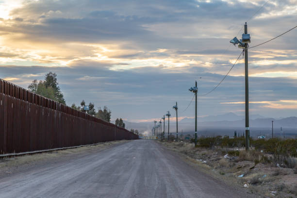 The US-Mexico Border Looking along the road running alongside the US-Mexico border, at dusk border patrol stock pictures, royalty-free photos & images
