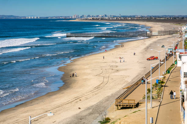 A panoramic view of Tijuana Beach and the steel wall on the US-Mexico border Tijuana, Mexico, May 23 - A panoramic view of the steel wall on the border between the United States and Mexico on the Pacific coast of Tijuana. In the foreground the beach of Playas of Tijuana, while in the background the Imperial Beach and the skyline of the city of San Diego. frontier field stock pictures, royalty-free photos & images