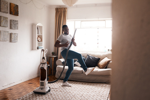 Shot of a young man dancing while busy vacuuming the living room