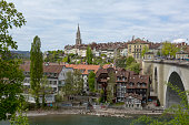 Bern, Switzerland - April 17, 2017: The variety of historic architecture of Bern. Townhouses on two levels in the city, cathedral and stone bridge over the river Aare can be seen. This is one of the countless wonderful places in Switzerland, which is a tourist attraction often visited by many tourists from all over the world.