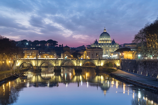 The Vatican city, the Saint Peter Cathedral in Rome city center with the Ponte Umberto I and the castle of Sant' Angelo at sunset. Beautiful dramatic sunset over the sky in Rome, motion water photo