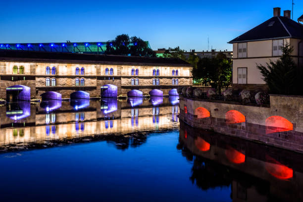the vauban dam illuminated at nightfall in the petite france historic quarter in strasbourg, france. - barragem do roxo imagens e fotografias de stock