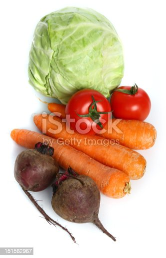 Three big  fresh carrots, the heads of cabbage, two tomatoes  and two beets on the  table