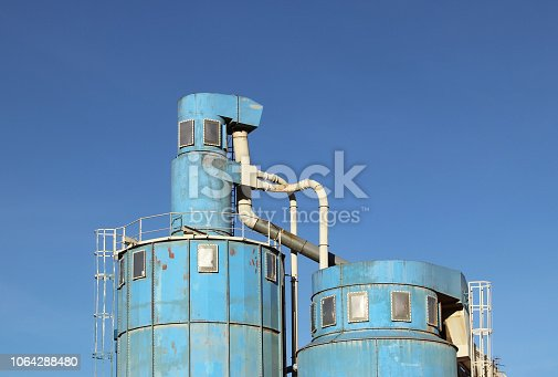 istock The ventilation system of the wood processing workshop. Metal construction for air circulation in a carpentry factory against a blue sky on a sunny day. Safety and working conditions in the enterprise 1064288480