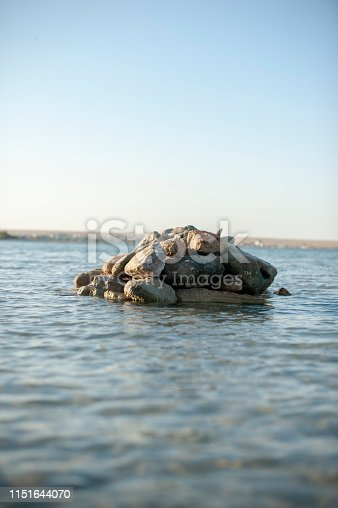 The vertical image is a seascape in the middle of a pile of large boulders tearing the horizon line. In the foreground in the unfocus through the clear water with small ripples can be seen the rocky bottom.
