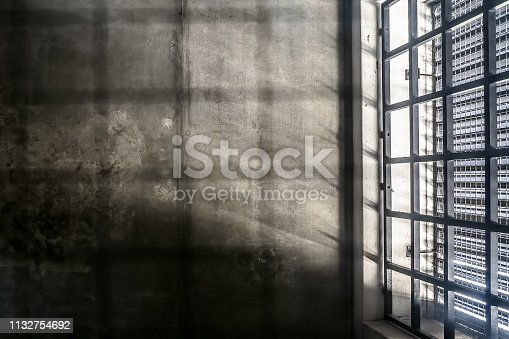 The very sober interior of a prison cell: barred windows with little light coming in and bare concrete walls. You should not want to be here
