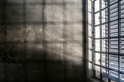 The very sober interior of a prison cell: barred windows with little light coming in and bare concrete walls