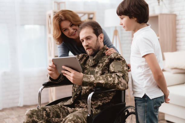 the veteran in a wheelchair came back from the army. a man in uniform in a wheelchair with his family. - military lifestyle stock pictures, royalty-free photos & images