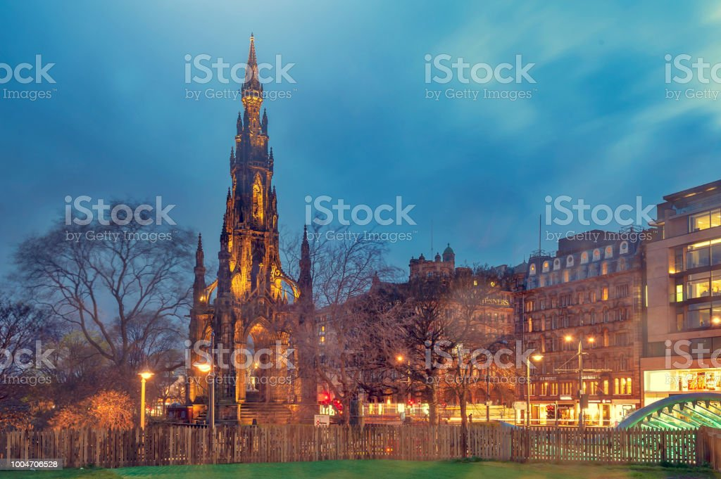 The Victorian Gothic building of Scott Monument to Scottish author, Sir Walter Scott, in Princes Street Gardens in old town Edinburgh, Scotland, UK, being lit up at night stock photo