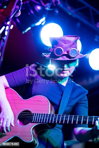 The video portrait of the mature, 45-years-old, woman, musician and singer, wearing the steampunk costume with the hat and googles, playing the acoustic guitar and singing in the live performance in the nightclub. The closeup video footage with the stage changing colorful lighting.