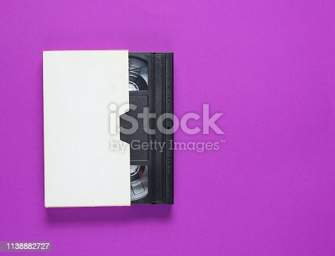 The videotape in a paper case on purple background. Pop culture attributes, minimalism. Top view