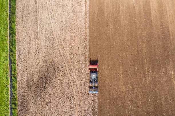 The view from a drone looking directly down on a tractor being used to pull a seed drill on a Scottish farm on a late summer day The view from a drone of a tractor pulling a seed drill which is sowing wheat to be harvested next year. The location is a rural area of Dumfries and Galloway in south west Scotland. johnfscott stock pictures, royalty-free photos & images