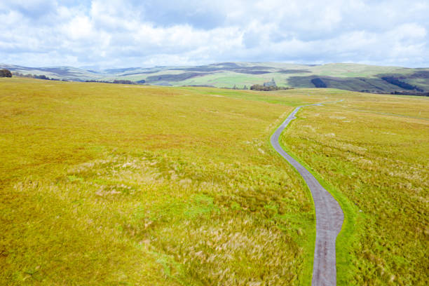 The view from a drone of a single lane road running through remote open Scottish countryside The view from a drone of a narrow road running through uncultivated Scottish countryside. The location is in Dumfries and Galloway, south west Scotland. johnfscott stock pictures, royalty-free photos & images
