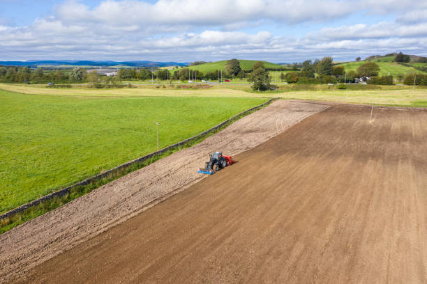 The view from a drone of a tractor being used to pull a seed drill on a Scottish farm on a late summer day The view from a drone of a tractor pulling a seed drill which is sowing wheat to be harvested next year. The location is a rural area of Dumfries and Galloway in south west Scotland. johnfscott stock pictures, royalty-free photos & images