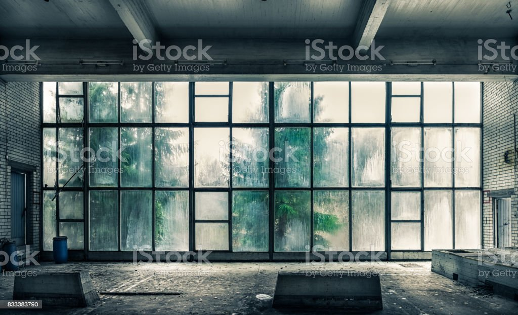 The view from an old, abandoned factory on the inside with nice window light stock photo