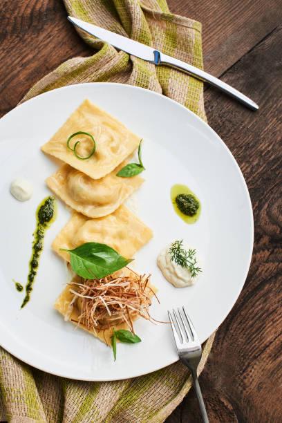 Der Blick vom oberen Abendessen von Ravioli mit Ente und Sahnesauce auf einem weißen Teller serviert – Foto