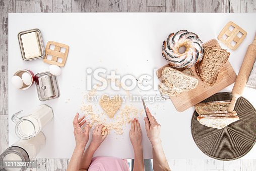 The view from the top. Mom and daughter prepare pastries in the kitchen. The concept of a loving family and family values. Healthy home food.