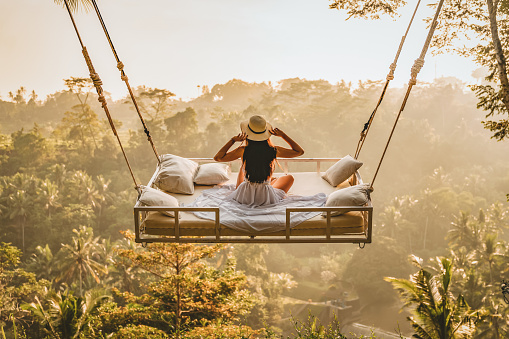 Photo of a young woman sitting on the swing, holding her hat.  Jungle Bed hanging over the tropical forest with Caucasian female resting while looking at the view, Bali, Indonesia.