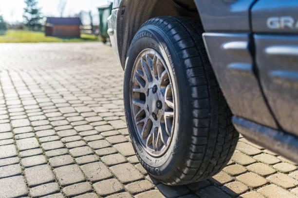 Der Blick auf das vordere, linke Rad mit Aluminiumfelge, der im Jahr 2002 mit einem Dieselmotor mit Automatikgetriebe hergestellt wurde. Auto in Graphitfarbe. – Foto