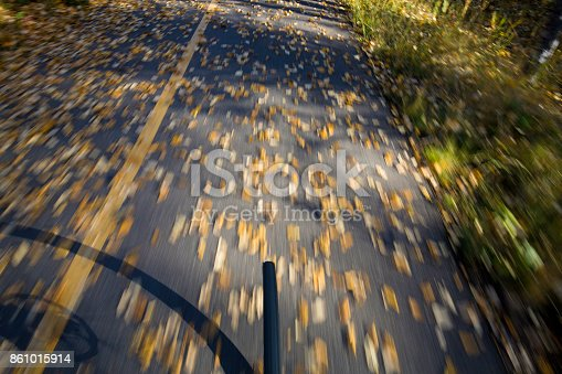 861018326 istock photo The view of the front wheel of a cyclo-cross commuter bike and the aspen leaves on a bicycle pathway in fall. 861015914