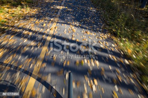 861018326 istock photo The view of the front wheel of a cyclo-cross commuter bike and the aspen leaves on a bicycle pathway in fall. 861015994