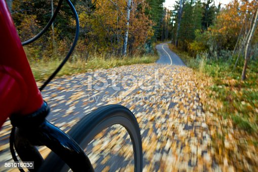 861018326 istock photo The view of the front wheel of a cyclo-cross commuter bike and the aspen leaves on a bicycle pathway in fall. 861016030