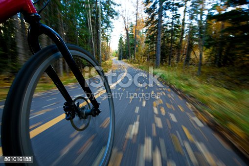 861018326 istock photo The view of the front wheel of a cyclo-cross commuter bike and the aspen leaves on a bicycle pathway in fall. 861016188