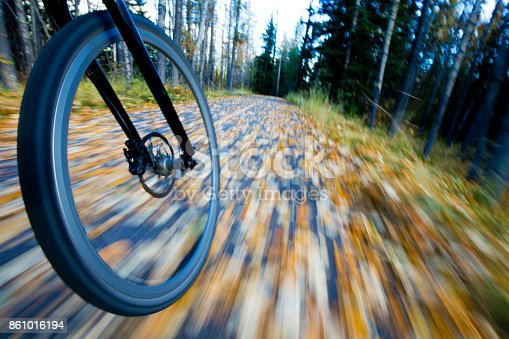 861018326 istock photo The view of the front wheel of a cyclo-cross commuter bike and the aspen leaves on a bicycle pathway in fall. 861016194