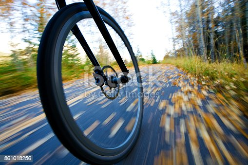 861018326 istock photo The view of the front wheel of a cyclo-cross commuter bike and the aspen leaves on a bicycle pathway in fall. 861018256
