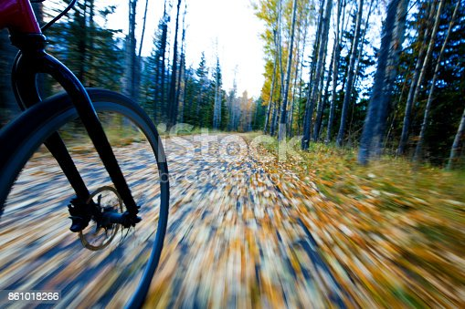 861018326 istock photo The view of the front wheel of a cyclo-cross commuter bike and the aspen leaves on a bicycle pathway in fall. 861018266