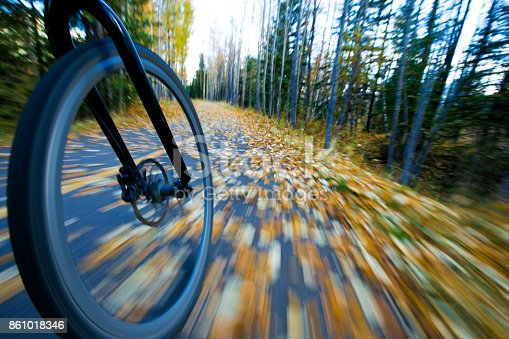 861018326 istock photo The view of the front wheel of a cyclo-cross commuter bike and the aspen leaves on a bicycle pathway in fall. 861018346