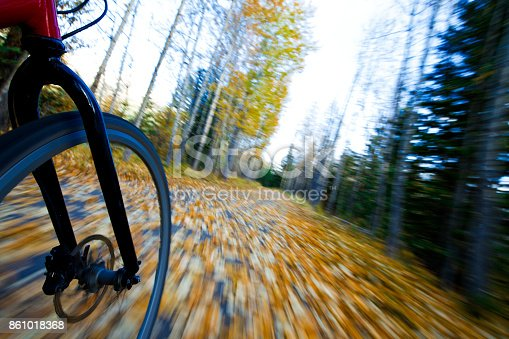 861018326 istock photo The view of the front wheel of a cyclo-cross commuter bike and the aspen leaves on a bicycle pathway in fall. 861018368